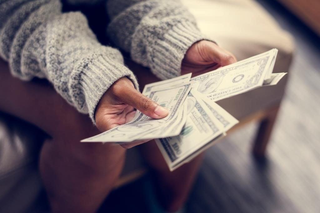 жена в близък план държи банкноти