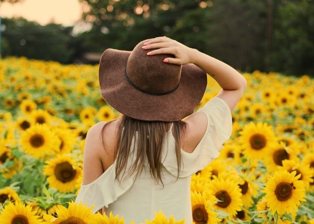 жена с капела на глават в слъчогледово поле