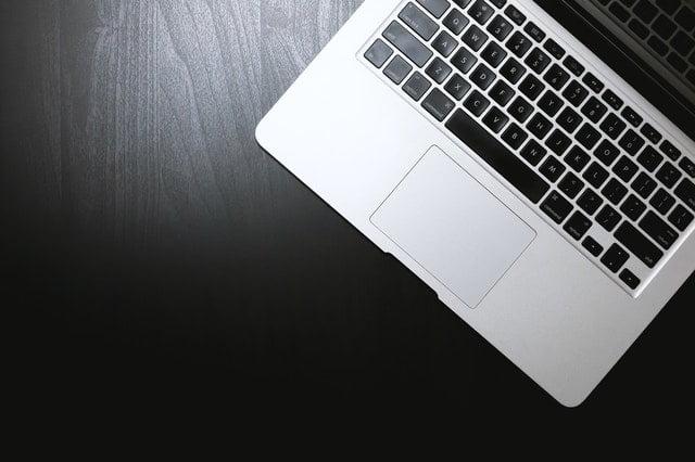 част от клавиатурата на лаптоп поставена върху черен плот