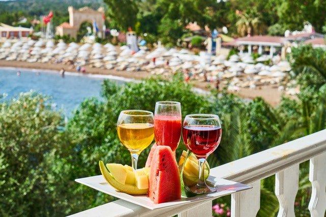 чиния с плодове и напитки на фона на залив с чадъри